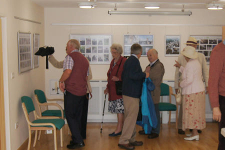 people looking at photo exhibition in Ty Price